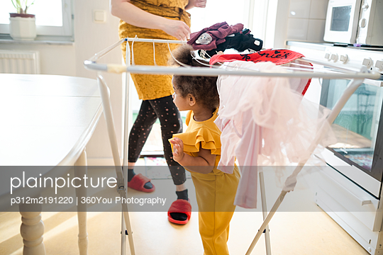 Toddler girl standing under drying rack - p312m2191220 by 360You Photography