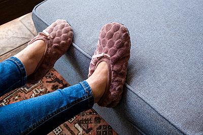Slippers on th sofa, stay at home due to Covid-19 - p1057m2185219 by Stephen Shepherd