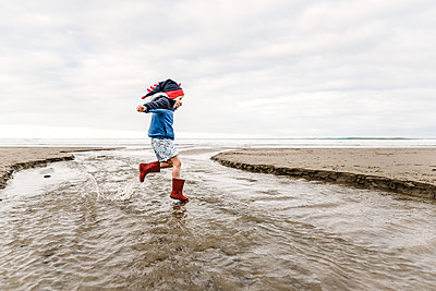 Young child wearing knit dinosaur hat jumping at beach - p1166m2171914 by Cavan Images