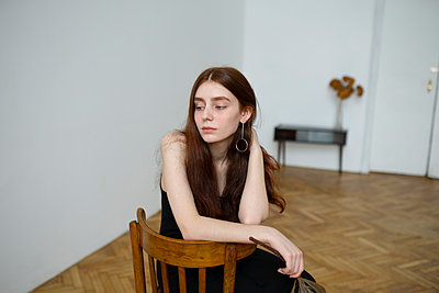 Young woman with brown hair on a chair - p1646m2237680 by Slava Chistyakov