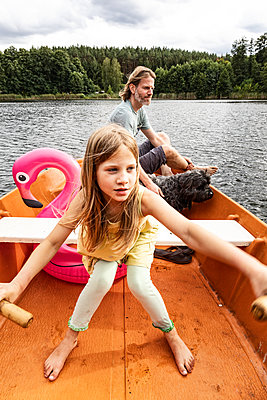 Father and daughter in a rowing boat - p294m2206276 by Paolo