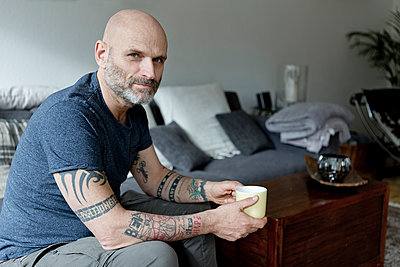 Tattooed man at home sitting on couch, drinking coffee - p300m1587860 by FL photography
