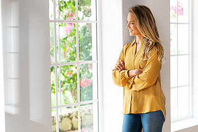Smiling woman leaning on wall looking through window in living room - p300m2276402 by Steve Brookland