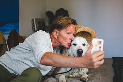 Senior man kissing dog while taking selfie on smart phone in bedroom at home - p426m2046397 by Maskot