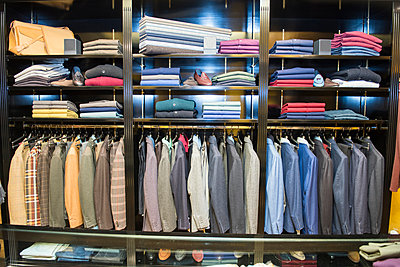 Rows of suit jackets in traditional tailors shop - p429m2004272 by G. Mazzarini