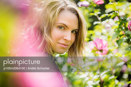 Portrait einer jungen Frau zwischen Blüten - p105m2064100 von André Schuster