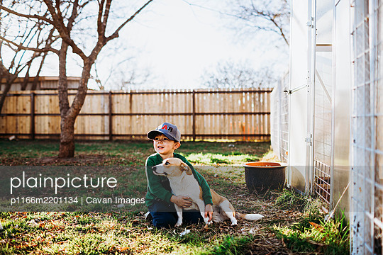 Young boy hugging corgi dog while sitting outside backyard greenhouse - p1166m2201134 by Cavan Images