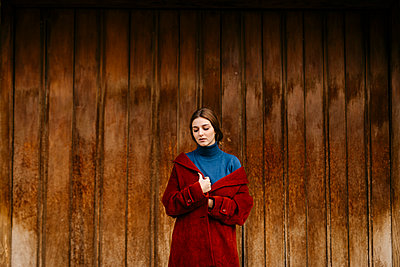 Close up portrait of woman with blue turtleneck pullover and red coat in front of a wooden door - p300m2160308 by Tania Cervián