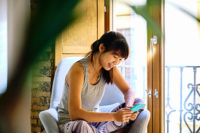 Smiling woman using mobile phone while sitting on chair at home - p300m2264814 by Antonio Ovejero Diaz
