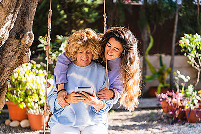 Daughter with arm around mother using digital tablet while sitting on swing at back yard - p300m2276870 by Manu Padilla Photo