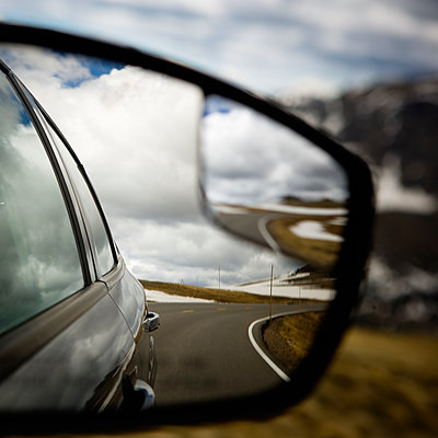 Mountain road and cloudy sky from a cars view mirror. - p343m1554738 by Ron Koeberer