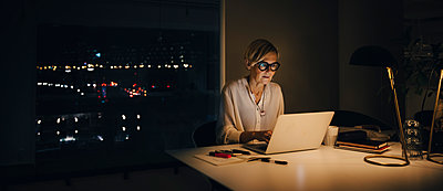 Mature female professional working late while using laptop at illuminated desk in office - p426m2194767 by Maskot