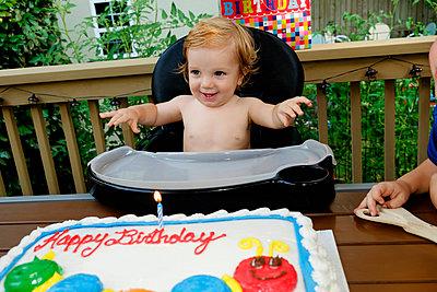 Caucasian baby boy in high chair near birthday cake - p555m1302057 by Roberto Westbrook