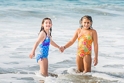 Girls holding hands in ocean waves - p555m1420463 by Sollina Images