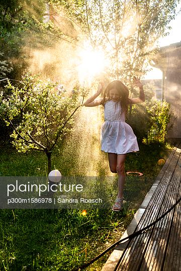 Girl having fun with garden hose in summer - p300m1586978 von Sandra Roesch