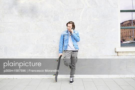 Young man holding skateboard, using smartphone - p300m1587596 von Francesco Morandini