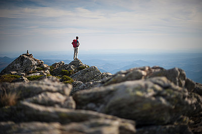 Man standing at the top of a mountain - p1007m1144447 by Tilby Vattard