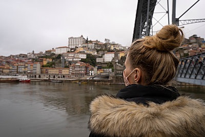 Tourist wears face mask and admire Dom Luis I bridge and Douro river - p1166m2255016 by Cavan Images