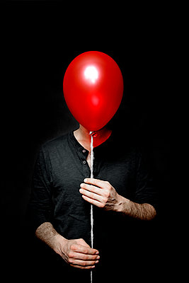 Man with a red balloon in front of his face - p1521m2150064 by Charlotte Zobel