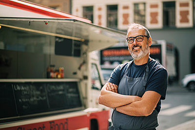 Portrait of confident chef with arms crossed standing by food truck on street - p426m1114878f by Maskot