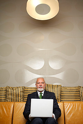 Mature businessman sitting on a sofa using a laptop - p4733743f by Stock4B