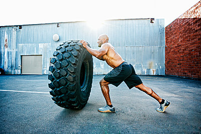Black man working out with heavy tire outdoors - p555m1304132 by Peathegee Inc