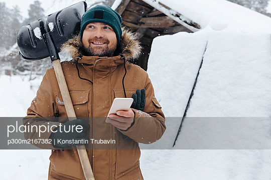 Portrait of smiling man with snow shovel and cell phone - p300m2167382 by Konstantin Trubavin