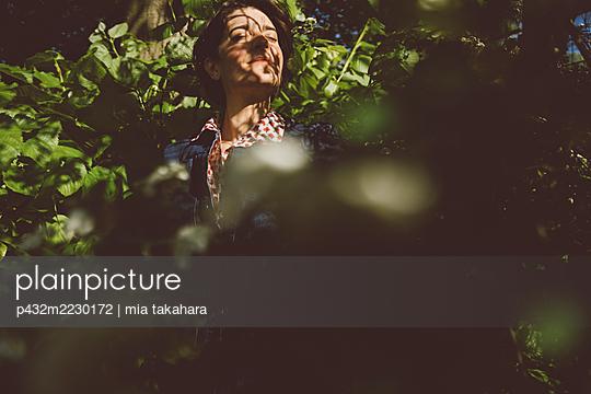 Frau steht verträumt in der Natur - p432m2230172 von mia takahara