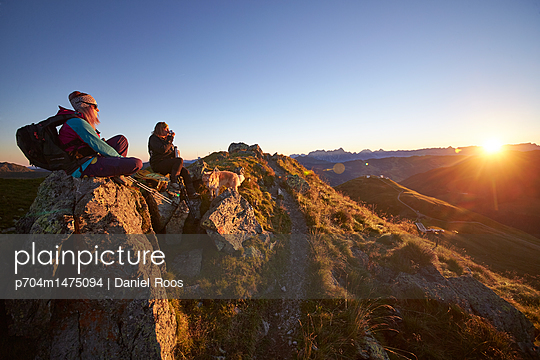 Mountaineers watching the sunrise at mountain peak - p704m1475094 by Daniel Roos