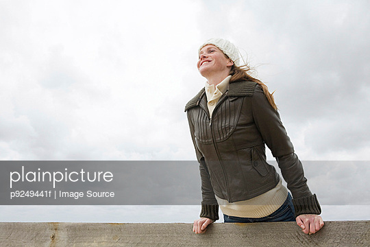 Woman leaning over wall - p9249441f by Image Source
