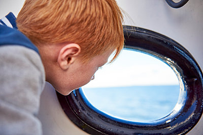 Boy looking out of the porthole - p300m2029272 by Jess Derboven