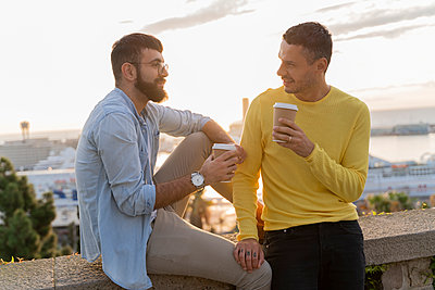 Gay couple with takeaway coffee on lookout above the city with view to the port, Barcelona, Spain - p300m2154491 by VITTA GALLERY