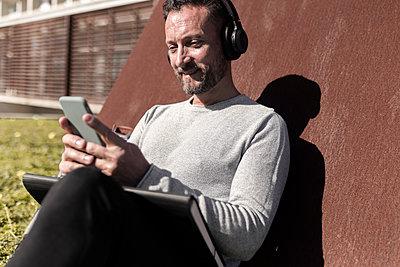 Mature man listening music through headphones while using smart phone - p300m2252374 by Sus Pons