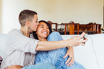 Lesbian couple at home using smartphone taking selfie - Milan, Lombardy, Italy - diversity, queer family, relationship concept - p300m2294053 von Eugenio Marongiu
