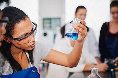 Young multi-ethnic chemistry students mixing solutions at laboratory in university - p426m1570068 by Maskot