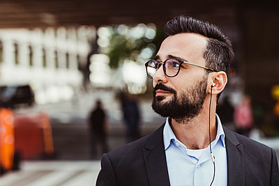 Confident businessman with in-ear headphones looking away while standing outdoors - p426m2169625 by Maskot