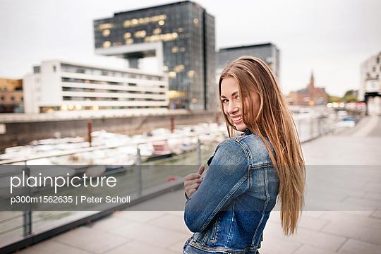 plainpicture - plainpicture p300m1562635 - Portrait of happy young wom... - plainpicture/Westend61/Peter Scholl
