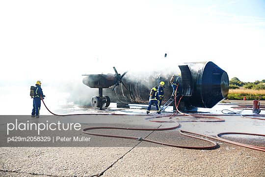 Firemen putting out fire on old training aeroplane, Darlington, UK - p429m2058329 by Peter Muller
