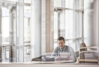 A man sitting in an open plan office by windows looking at a laptop. - p1100m1095642 by Mint Images