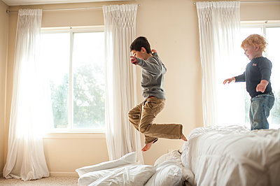 Brother having fun jumping off bed into pillows in bedroom - p1166m2073752 by Cavan Images