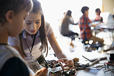 Pre-adolescent boy and girl assembling robotics in classroom - p1192m1231108 by Hero Images