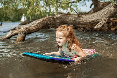 Mädchen schwimmt am See auf einem Bodyboard - p1394m1541475 von benjamin tafel