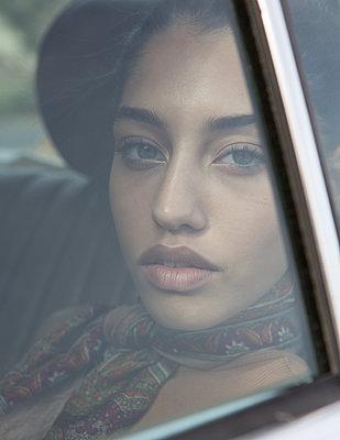 Teenage girl looking through car window - p1640m2260114 by Holly & John