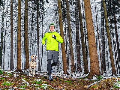 Male athlete jogging in snow with Labrador Retriever at forest - p300m2256631 by Stefan Schurr