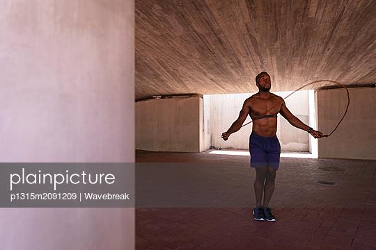 Man skipping with rope under the bridge - p1315m2091209 by Wavebreak