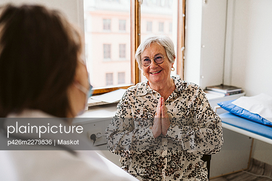 Smiling senior female patient with hands clasped looking at doctor a medical clinic - p426m2279836 by Maskot