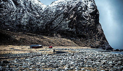 One person walking towards a building at the base of a mountain across a rocky beach. - p1100m1482235 by Mint Images