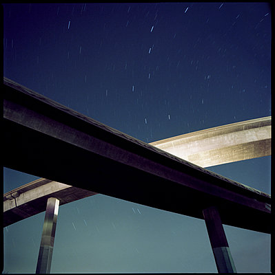 Low angle view of overpass against star trails - p1166m1194008 by Cavan Images