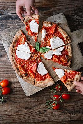Eating a pizza with mozzarella, hand taking pizza slice - p300m2083102 von Alberto Bogo