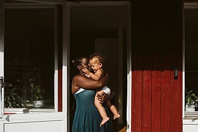Mother with toddler in front of house - p312m2161959 by Stina Gränfors